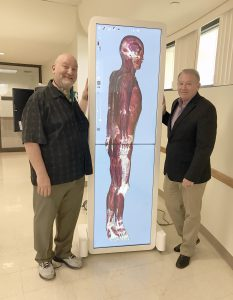 Keiser University faculty member Scott Sachs and Dept. Chair Shawn McPartland with the Anatomage device